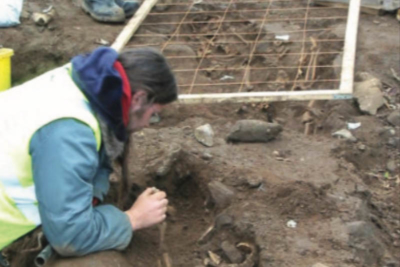 An image of Archaeologist Dylan Foley carefully excavating a skeleton at Ballyhanna (TII)